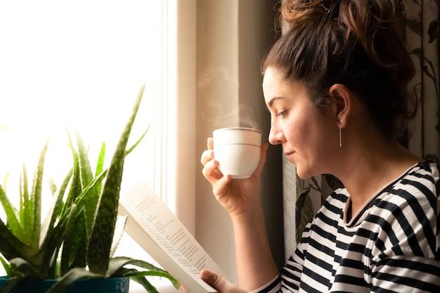 Mujer caucásica adulta sentada cerca de la ventana en casa relajándose en su sala de estar leyendo un libro y bebiendo café o té