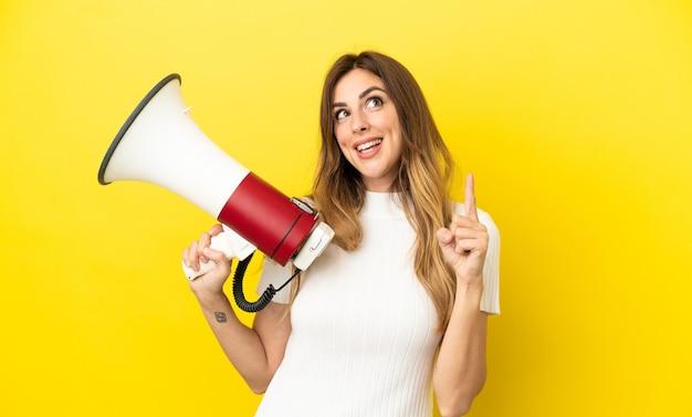 Mujer caucásica aislada sobre fondo amarillo sosteniendo un megáfono y con la intención de darse cuenta de la solución