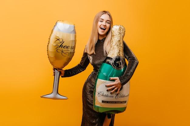 Mujer caucásica alegre divertida posando con champán. increíble mujer bien vestida celebrando cumpleaños y bromeando en la fiesta.