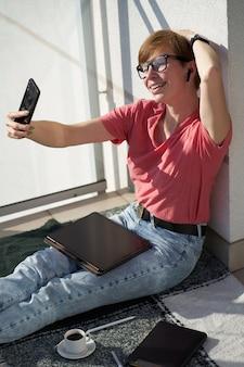 Mujer caucásica artista digital haciendo selfie en smartphone, sentado en cuadros con taza de café en el balcón. concepto independiente