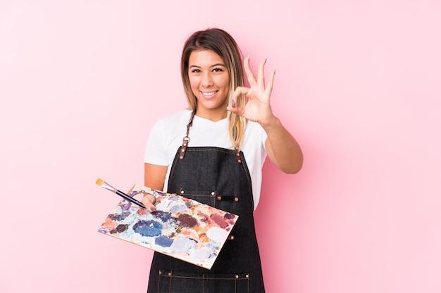 La mujer caucásica del artista joven que sostenía un palett aisló alegre y confiado que mostraba gesto aceptable.