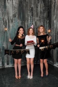 Mujer caucásica atractiva joven con una torta de cumpleaños entre sus amigos