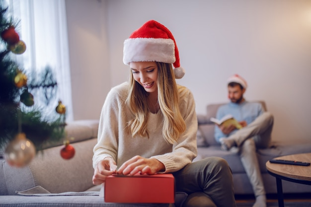 Mujer caucásica atractiva sonriente en suéter y con el sombrero de santa en la cabeza que se sienta en el sofá en sala de estar al lado del árbol de navidad y regalos del embalaje. en el fondo su novio sentado y leyendo el libro.