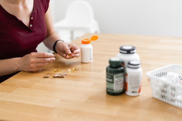 La mujer caucásica bebe muchas píldoras. medicina preventiva. suplementos alimenticios