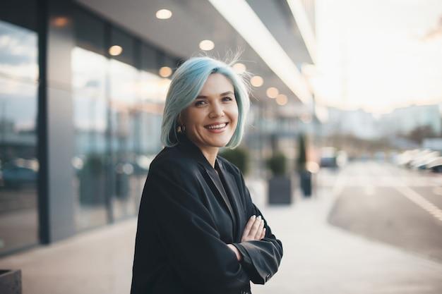 Mujer caucásica con cabello azul posando con las manos cruzadas y sonrisa al frente en la calle