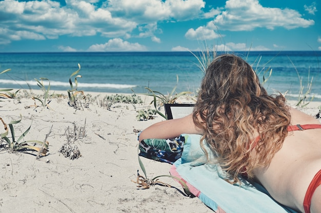 Mujer caucásica con cabello largo, vistiendo un bikini rojo, tumbado en la playa junto al mar azul