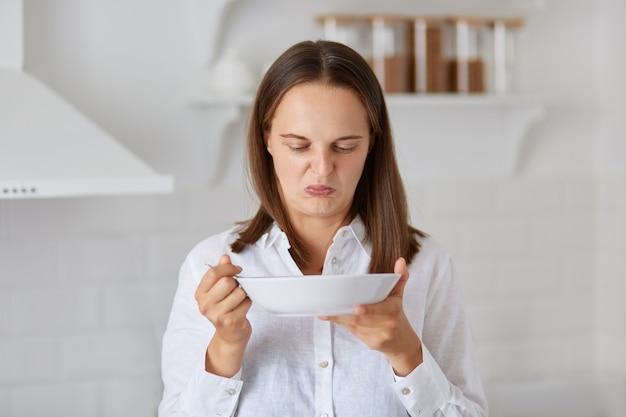 Mujer caucásica de cabello oscuro con camisa blanca demuestra disgusto torciendo la cara con reacción negativa mientras trata de comer un poco de sopa maloliente de un plato en la cocina.