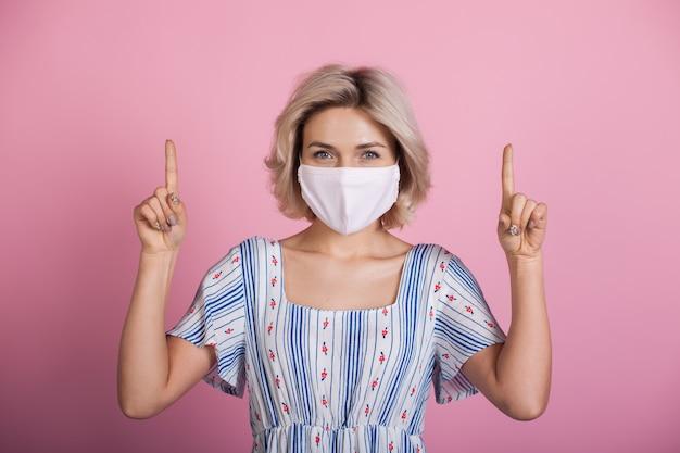 Mujer caucásica con cabello rubio con máscara médica y vestido apuntando hacia arriba con los dedos índices y sonriendo a la cámara