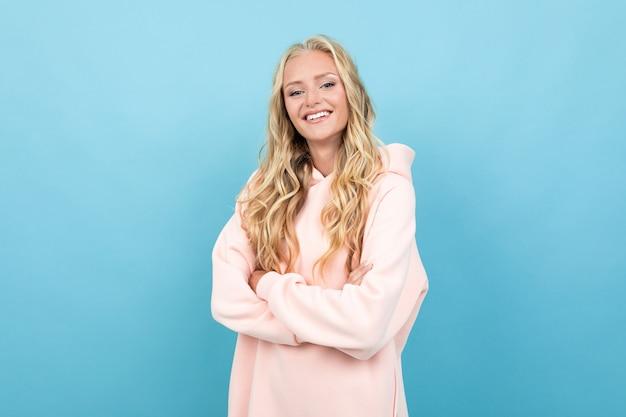 Mujer caucásica con cabello rubio en rosa con capucha sonrisas aisladas en azul