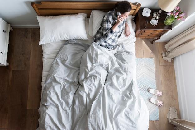 Mujer caucásica en cama hablando por teléfono