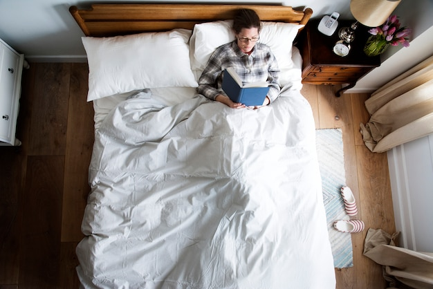 Mujer caucásica en cama leyendo un libro