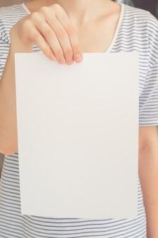 La mujer caucásica en camiseta rayada sostiene una hoja blanca del papel en blanco en la mano