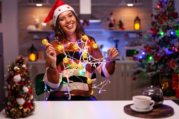 Mujer caucásica decorar el árbol de navidad con luces