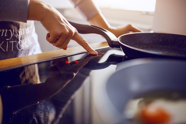 Mujer caucásica en delantal de ajuste de temperatura en estufa