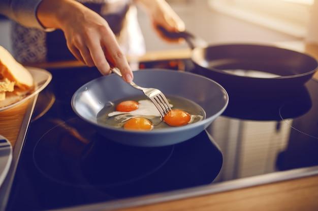 Mujer caucásica en delantal de pie junto a la estufa y preparar el lado soleado hacia arriba