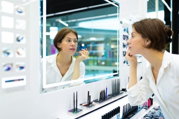 Mujer caucásica con delineador de ojos azules en la tienda de maquillaje