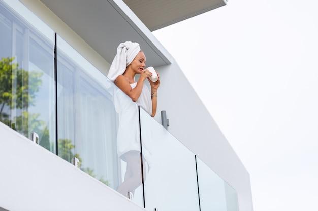 Mujer caucásica después de la ducha en toalla se encuentra en el balcón de la villa y beber café o té comienzo perfecto del día mujer relajada tranquila se encuentra con el nuevo día