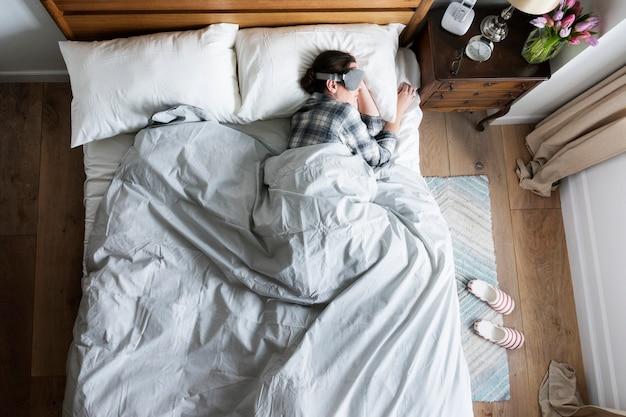 Mujer caucásica durmiendo con una cubierta de ojo en