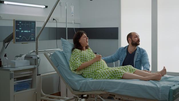 Mujer caucásica con embarazo que tiene contracciones dolorosas con el marido de la mano. enfermera afroamericana dando apoyo para el parto en la sala del hospital. pareja esperando bebé