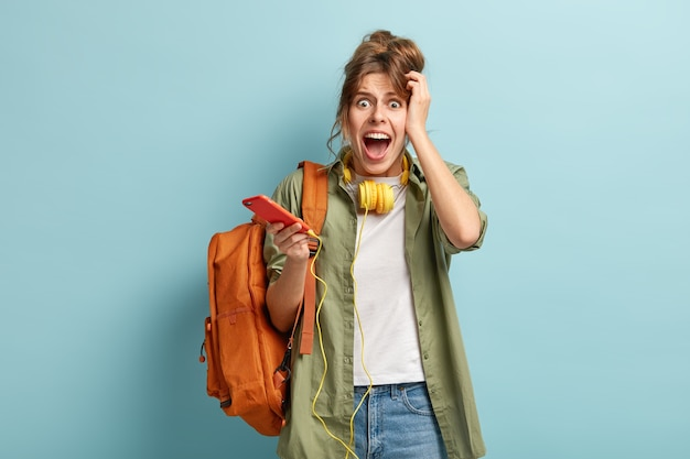 Mujer caucásica emocional frustrada grita desesperadamente, tiene mala conexión a internet, no puede hacer videollamadas
