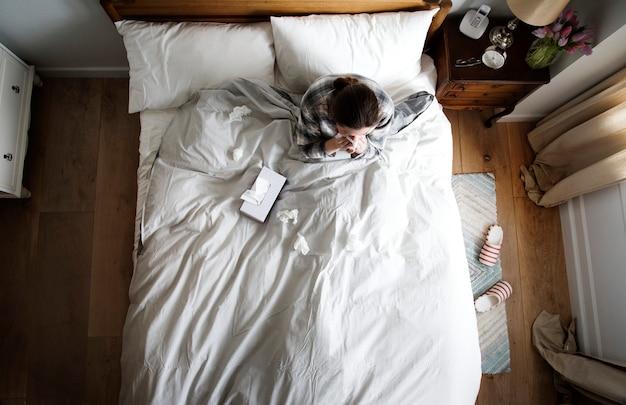 Mujer caucásica enferma en cama soplando su nariz