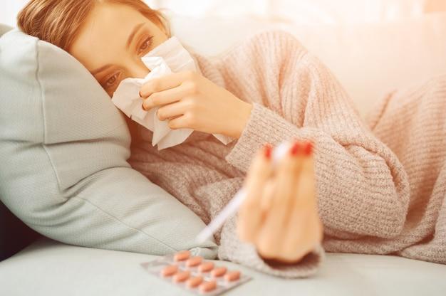 Mujer caucásica enferma con papel de seda en la cama con termómetro y pastillas