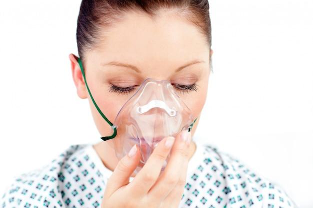 Mujer caucásica enferma que lleva una máscara