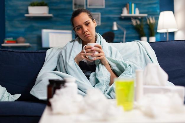 Mujer caucásica enferma sentada en la cama con gripe y resfriado severo
