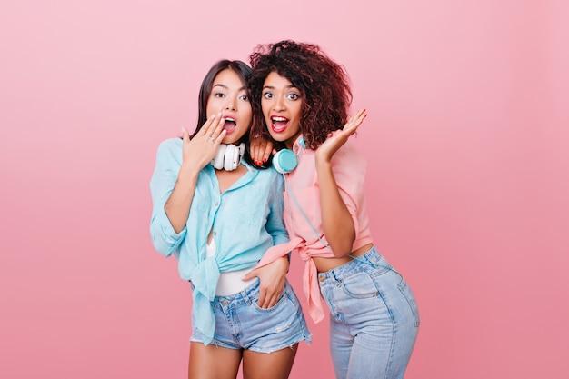 Mujer caucásica entusiasta con expresión de la cara sorprendida posando junto a la chica rizada mulata. foto interior de damas conmocionadas en coloridas camisetas de pie.