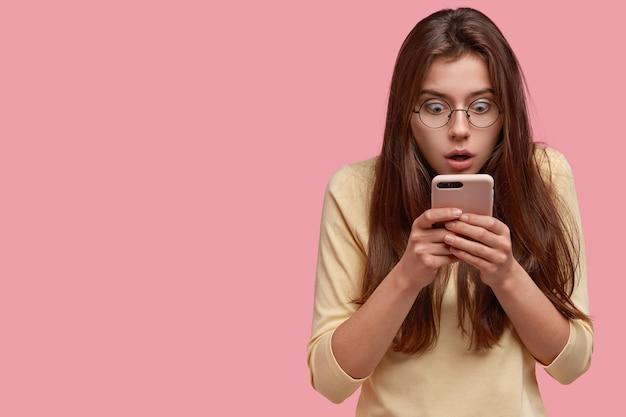Mujer caucásica estupefacta y perpleja revisa las noticias en las redes sociales en el teléfono celular, envía mensajes a un amigo, descubre noticias impactantes, mira la pantalla