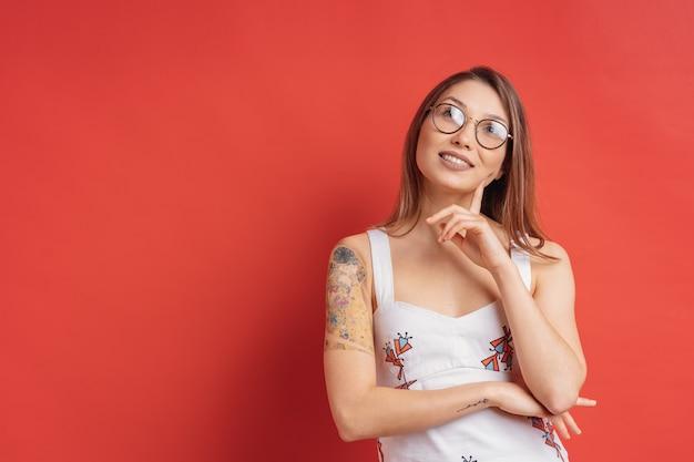 Mujer caucásica con gafas pensando e imaginación aislado en la pared roja