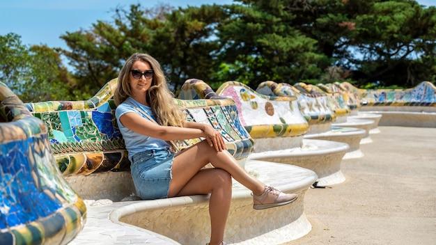 Mujer caucásica con gafas de sol en la plaza del parque güell sentado en los bancos
