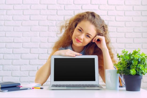 Mujer caucásica hermosa que se sienta y que trabaja en la computadora portátil
