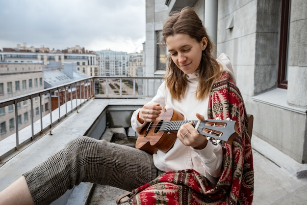 Mujer caucásica hipster / hippie en ropa casual tocando la guitarra hawaiana, canta una canción en un ukelele durante el autoaislamiento en la casa en la terraza.