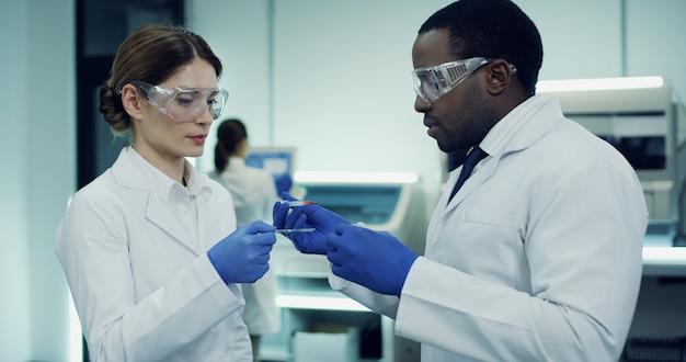 Mujer caucásica y hombre afroamericano, trabajadores del laboratorio médico, haciendo un análisis de sangre y discutiéndolo.