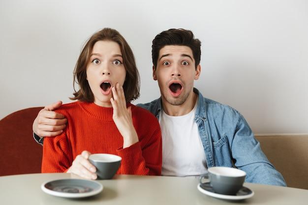 Mujer caucásica y hombre expresando sorpresa con la boca abierta, mientras bebe café o té en la cafetería