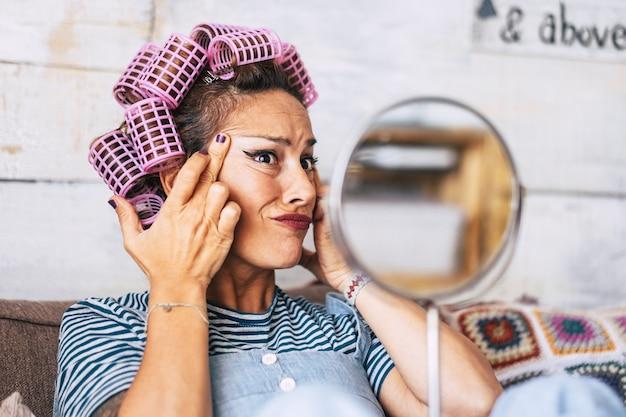 Mujer caucásica joven adulta preocupada comprobar las arrugas y el efecto del tiempo de envejecimiento en la piel de la cara