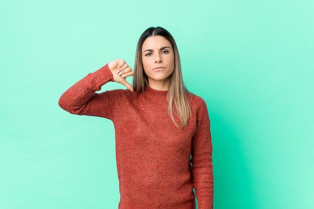Mujer caucásica joven aislada mostrando un gesto de aversión, pulgares abajo. concepto de desacuerdo