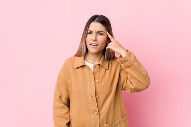 Mujer caucásica joven aislada mostrando un gesto de decepción con el dedo índice.