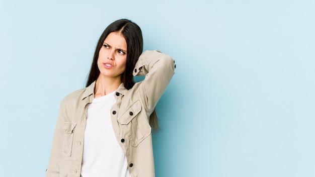 Mujer caucásica joven aislada en la pared azul que sufre dolor de cuello debido al estilo de vida sedentario.