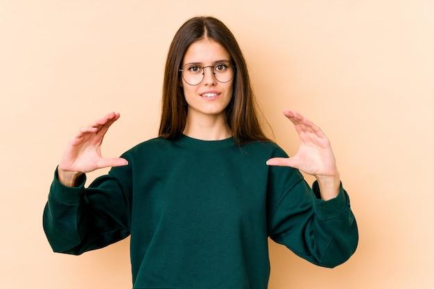 Mujer caucásica joven aislada en la pared beige que sostiene algo con las palmas