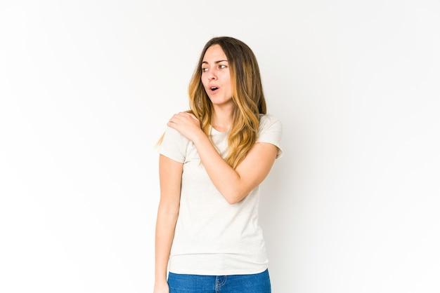 Mujer caucásica joven aislada en la pared blanca que tiene un dolor de hombro.