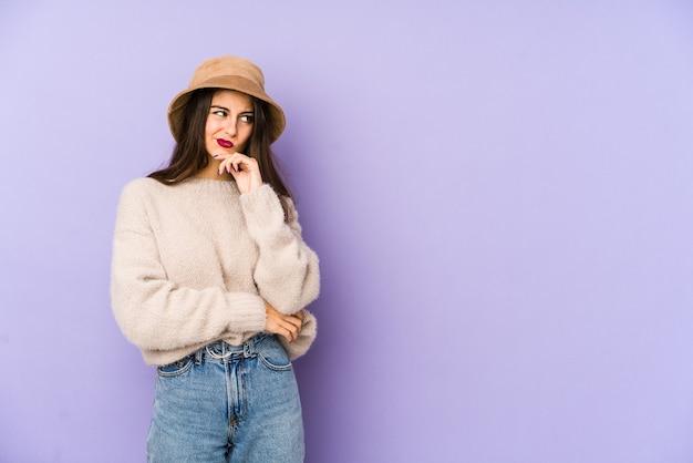 Mujer caucásica joven aislada en la pared púrpura pensando y mirando hacia arriba, siendo reflexivo, contemplando, teniendo una fantasía.