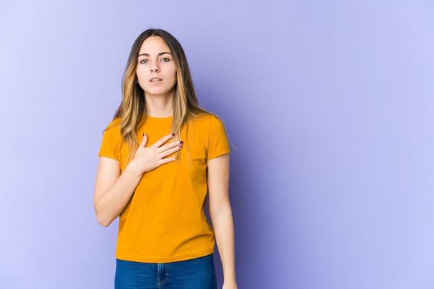 Mujer caucásica joven aislada en la pared púrpura que hace un juramento, poniendo la mano en el pecho.