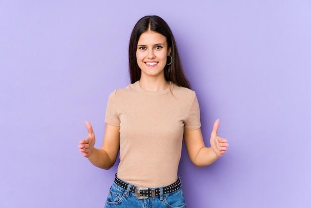 Mujer caucásica joven aislada en la pared púrpura que lleva a cabo algo con ambas manos, presentación del producto.