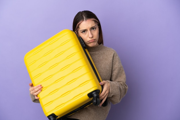 Mujer caucásica joven aislada en la pared púrpura en vacaciones con maleta de viaje e infeliz