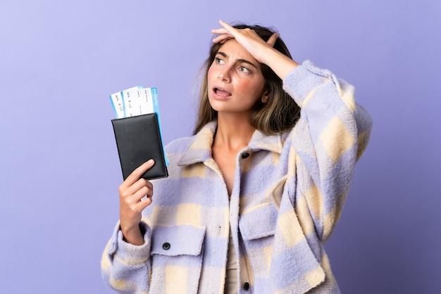Mujer caucásica joven aislada en la pared púrpura en vacaciones con pasaporte y boletos de avión mientras mira algo en la distancia