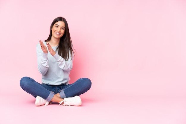 Mujer caucásica joven aislada en la pared rosa aplaudiendo después de la presentación en una conferencia