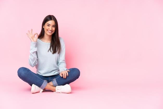 Mujer caucásica joven aislada en la pared rosada que muestra la muestra aceptable con los dedos