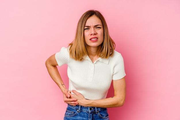 Mujer caucásica joven aislada en la pared rosada que tiene un dolor de hígado, dolor de estómago.